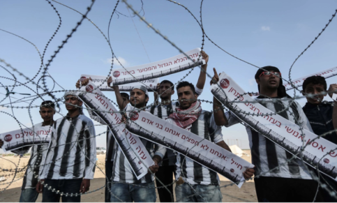 """Young Palestinians protestors at the Gaza border carry signs in Hebrew: """"Soldier, we are not objects, we are human beings.'"""